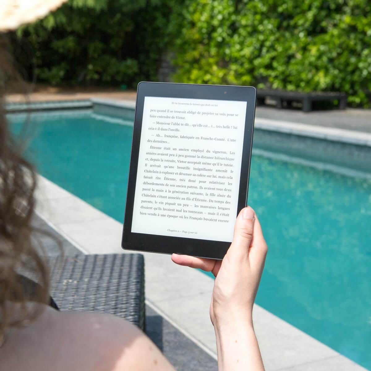 girl reading an Ipad beside the swimming pool